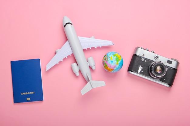 Pojęcie turystyki i podróży. globus, paszport, figurka samolotu pasażerskiego i aparat na różowej pastelowej ścianie widok z góry. leżał na płasko