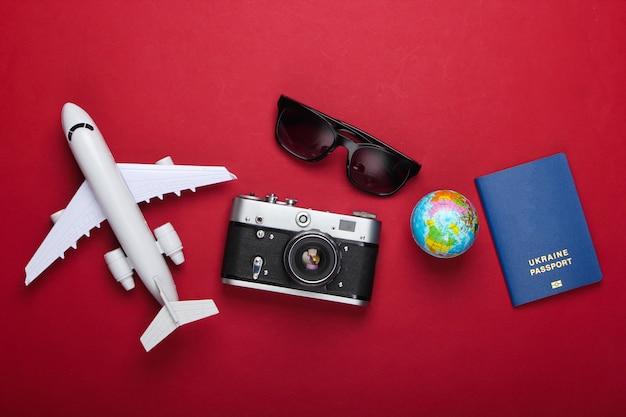 Pojęcie turystyki i podróży. globus, paszport, figurka samolotu pasażerskiego, okulary przeciwsłoneczne i aparat na czerwonym tle. widok z góry. leżał na płasko