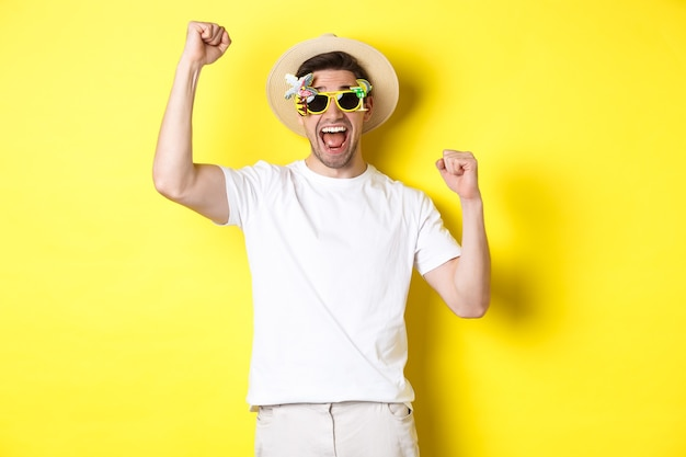 Pojęcie turystyki i stylu życia. szczęśliwy człowiek wygrywający wycieczkę do kurortu, krzyczący tak i podnoszący ręce do góry, triumfujący, noszący okulary przeciwsłoneczne i letni kapelusz, żółte tło.