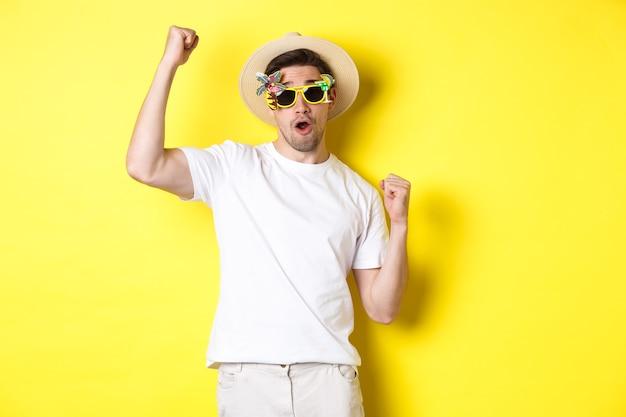 Pojęcie turystyki i stylu życia. szczęśliwy turysta facet cieszący się podróżą, kibicujący dla ciebie, pompka pięścią i triumfujący, jadący w podróż w letnim kapeluszu i okularach przeciwsłonecznych, żółte tło.