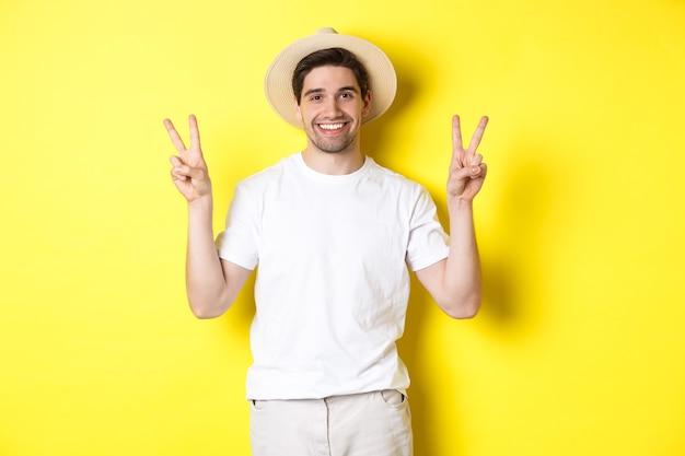 Pojęcie turystyki i wakacji. szczęśliwy turysta mężczyzna pozuje do zdjęcia ze znakami pokoju, uśmiechając się podekscytowany, stojąc na żółtym tle.