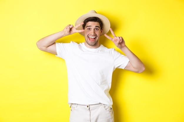 Pojęcie turystyki i wakacji. szczęśliwy turysta pozuje do zdjęcia ze znakami pokoju, uśmiechając się podekscytowany, stojąc na żółtym tle.