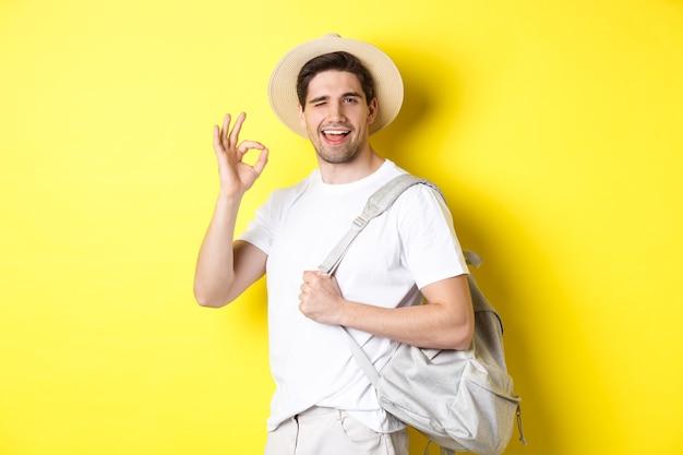 Pojęcie turystyki, podróży i wakacji. szczęśliwy turysta jedzie na wakacje, trzymając plecak i pokazując znak dobra, uśmiechnięty zadowolony, stojąc na żółtym tle.