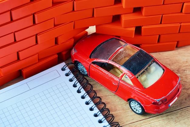 Pojęcie ubezpieczenia samochodu. czerwony samochód rozbił się w ścianie z cegły