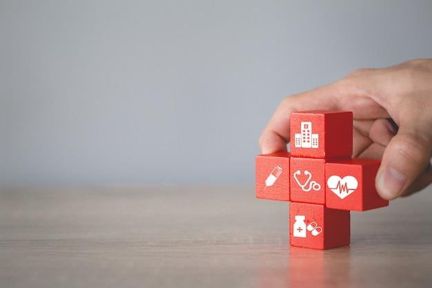 Pojęcie ubezpieczenia zdrowotnego, układanie bloków drewnianych z ikoną opieki zdrowotnej medycznej.