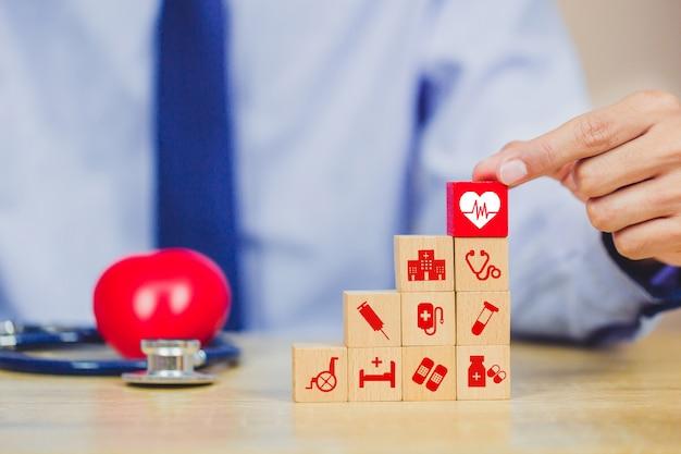 Pojęcie ubezpieczenia zdrowotnego, układanie strony bloku drewna układanie z ikoną opieki zdrowotnej medycznej