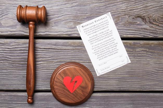 Pojęcie umowy małżeństwa i rozwodu. drewniany młotek z pękniętym sercem i kurczem.