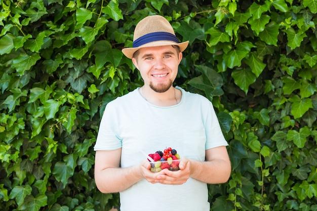 Pojęcie wegetarian, surowej żywności i diet - zbliżenie człowieka trzymać owoce i jagody.