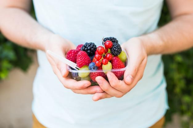 Pojęcie wegetarian, surowej żywności i diet - zbliżenie rąk człowieka trzymają owoce i jagody.