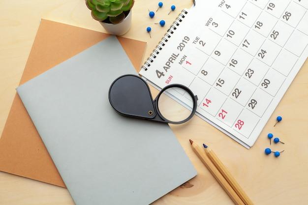 Pojęcie wizerunku biznesu i spotkań. kalendarz przypominający o ważnym spotkaniu i lupę