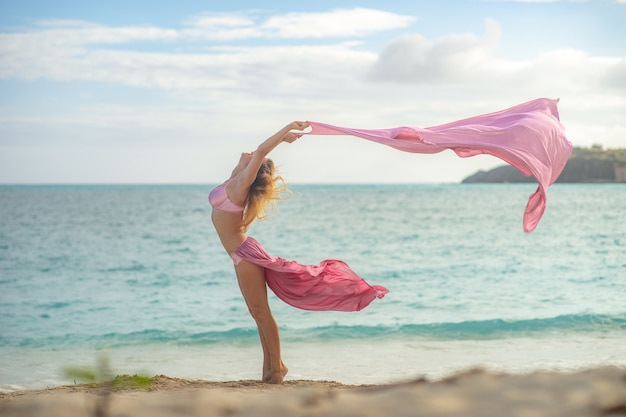 Pojęcie wolności i szczęścia. szczęśliwa kobieta na plaży latem z latającego różowego jedwabiu.