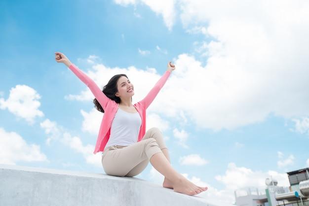 Pojęcie wolności. przyjemność. azjatycka młoda kobieta relaksuje się pod błękitnym niebem na dachu z rękami uniesionymi ku niebu