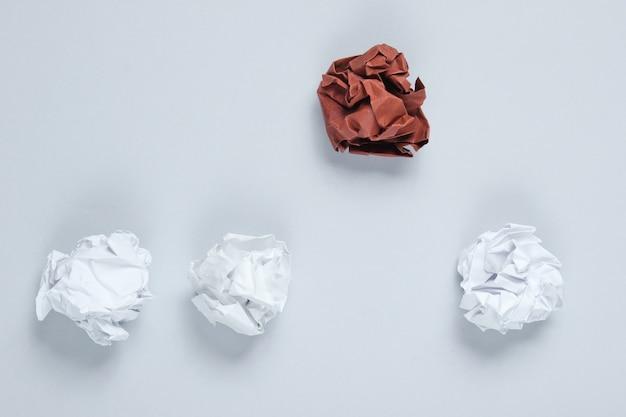 Pojęcie wyjątkowości, dyskryminacja rasowa. białe i brązowe zmięte papierowe kulki na szarym stole. widok z góry, minimalizm