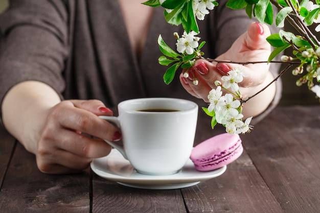 Pojęcie z poranną kawą w romantycznym stylu na drewnianym tle. kwiaty wiśni, kawa i ręka