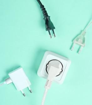 Pojęcie zależności elektrycznej. wiele wtyczek w pobliżu gniazdek na niebieskim tle