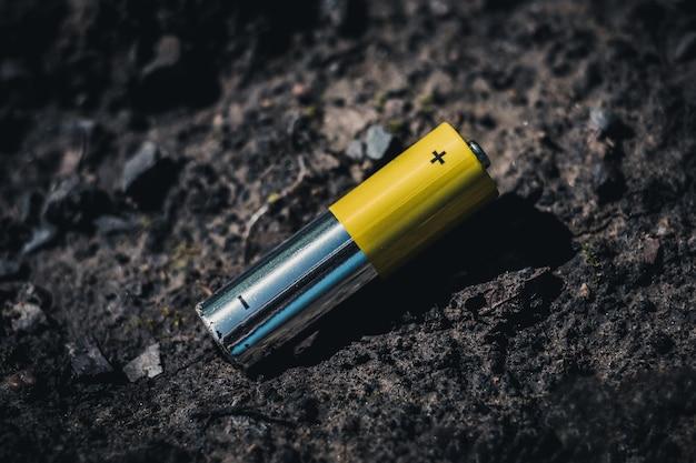 Pojęcie zanieczyszczenia gleby bateriami i akumulatorami. zużyty akumulator na ziemi.
