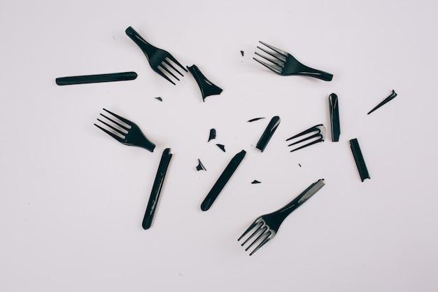 Pojęcie zanieczyszczenia tworzywami sztucznymi. nie zawiera plastiku. rozrzucone, złamane czarne widelce jednorazowego użytku