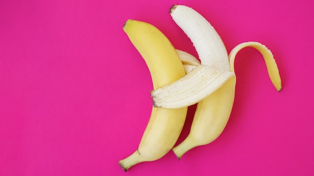 Pojęcie zaprzyjaźnionej pary. banan jak mąż obejmuje drugiego jak żonę. pomysł na parę gejów. stałe różowe tło.