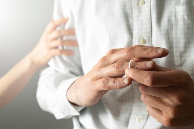 Pojęcie zdrady. mężczyzna zdradza żonę, usuwając pierścionek zaręczynowy.