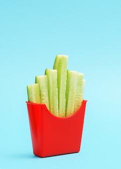 Pojęcie zdrowego odżywiania. filiżanka frytek z pokrojonymi w plasterki ogórkami.