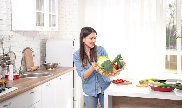 Pojęcie zdrowego odżywiania. młoda piękna kobieta w kuchni z owocami i warzywami. wegańskie jedzenie