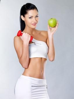 Pojęcie zdrowego stylu życia dla kobiety stoi z zielonym jabłkiem.