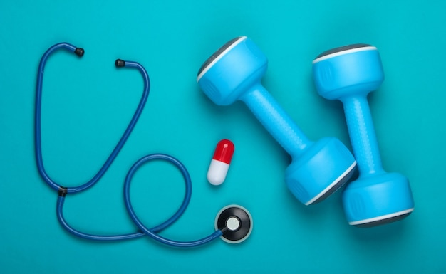 Pojęcie zdrowego stylu życia i opieki zdrowotnej. hantle ze stetoskopem, witaminy kapsułki na niebieskim tle. widok z góry