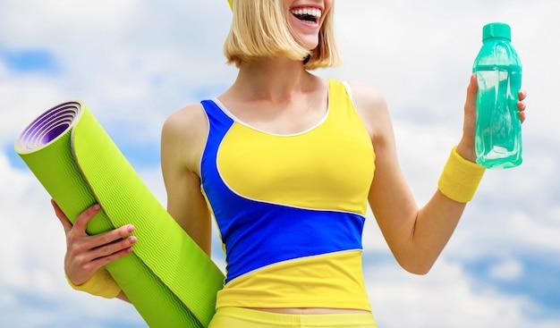 Pojęcie zdrowego stylu życia. kobieta w stroju sportowym trzyma matę do jogi i butelkę