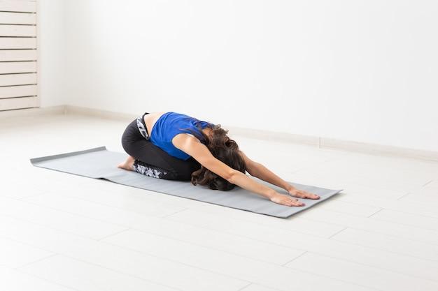 Pojęcie zdrowego stylu życia, ludzi i sportu. młoda kobieta robi joga na białym z kręconymi włosami