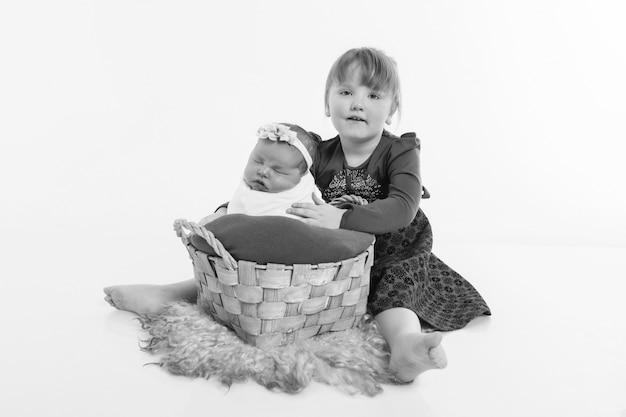 Pojęcie zdrowego stylu życia, ochrony dziecka, zapłodnienia in vitro z noworodkiem na podłodze. dziecko w koszyku. szczęśliwe dzieci: siostry