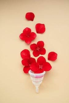 Pojęcie zdrowia kobiety. przezroczysty kubek menstruacyjny z czerwonymi kwiatami. widok z góry.