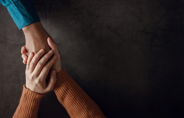 Pojęcie zdrowia psychicznego. para robi wygodny dotyk dłoni dla wspólnego zachęcania. miłość i troska. widok z góry