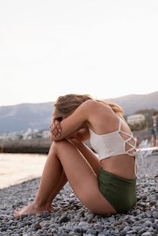 Pojęcie zdrowia psychicznego. widok z tyłu młodej kobiety z depresją w stroju kąpielowym, siedzącej na plaży, z rękami wokół nóg