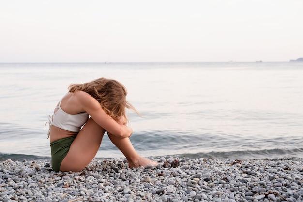 Pojęcie zdrowia psychicznego. widok z tyłu przygnębionej młodej kobiety w stroju kąpielowym, siedzącej na plaży, odwracającej wzrok