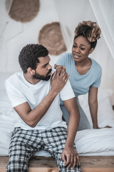 Pojednanie. smutny, młody ciemnoskóry mąż i zaniepokojona zmartwiona żona dotykają jego ramienia w domu na łóżku