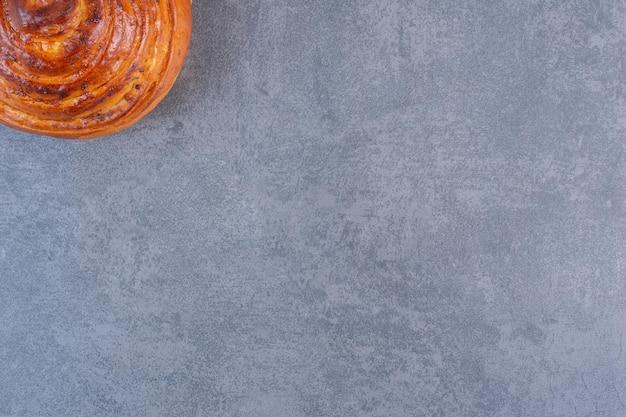 Pojedyncza, chrupiąca słodka bułka wyeksponowana na marmurowym tle. zdjęcie wysokiej jakości