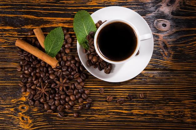 Pojedyncza filiżanka kawy z liśćmi i fasolą
