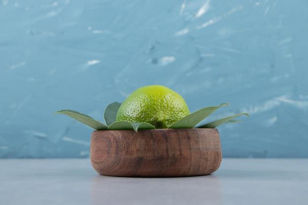 Pojedyncza limonka z liśćmi w drewnianej misce