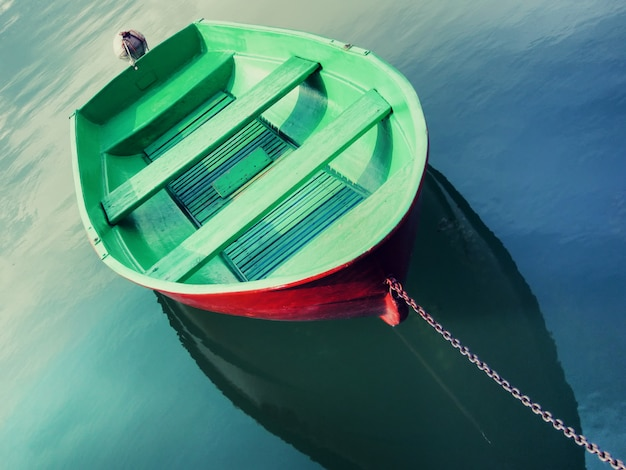 Pojedyncza łódź rybacka pomalowana na zielono unosząca się na wodzie i wiązana metalicznym łańcuchem