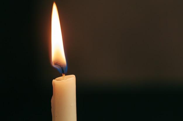 Pojedyncza płonąca świeca odizolowywająca z czernią