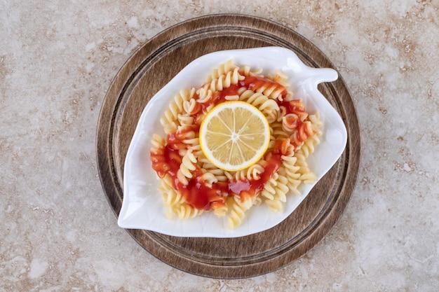 Pojedyncza porcja świeżo ugotowanego makaronu na marmurowej powierzchni.