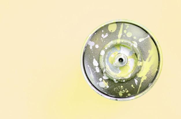 Pojedyncza puszka na spray do rysowania graffiti leży na pastelowym kolorowym tle