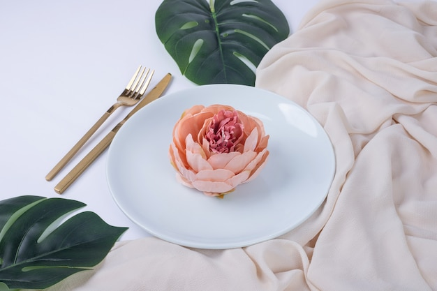 Pojedyncza róża na białym talerzu ze sztucznymi liśćmi i obrusem.