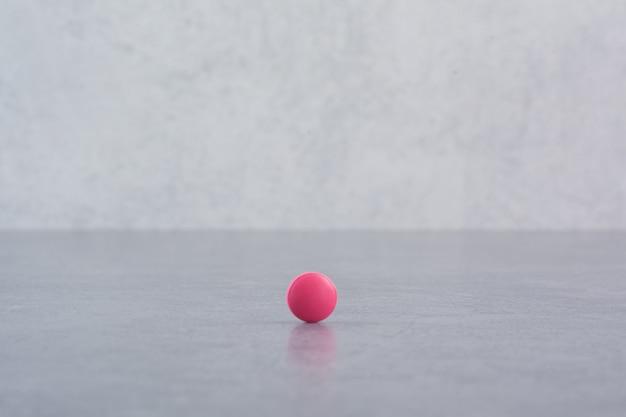 Pojedyncza różowa pigułka na marmurowym stole.