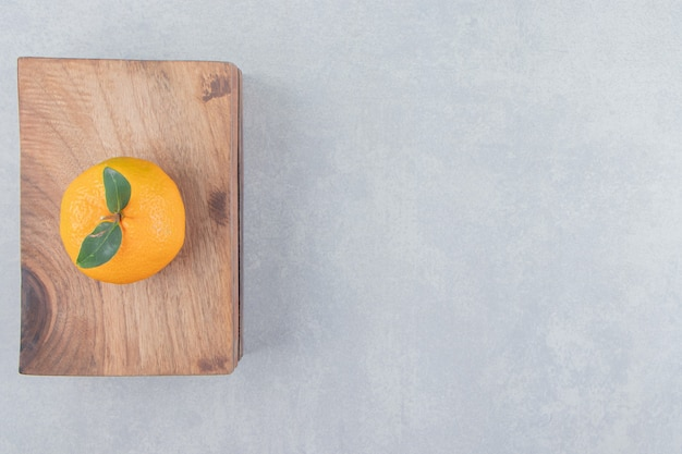 Pojedyncza smaczna klementynka na drewnianej desce