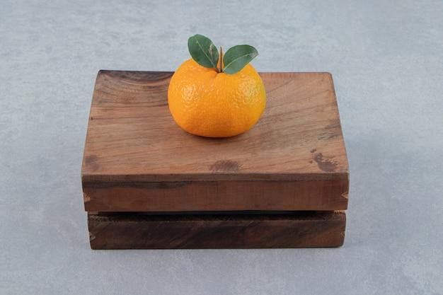 Pojedyncza smaczna klementynka na drewnianym pudełku.