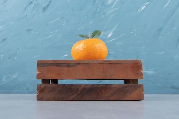 Pojedyncza smaczna klementynka na drewnianym pudełku