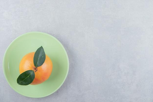 Pojedyncza świeża klementynka na zielonym talerzu