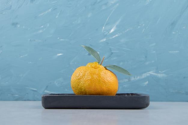 Pojedyncza świeża mandarynka z liśćmi na czarnym talerzu