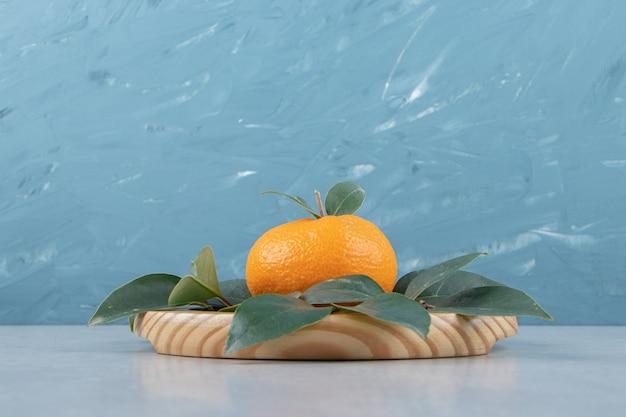 Pojedyncza świeża mandarynka z liśćmi na drewnianym talerzu.